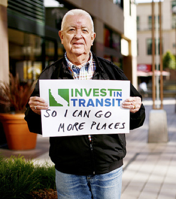 Man holding sign in support of transit