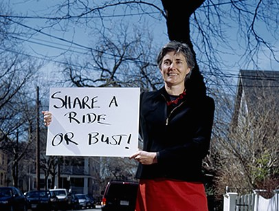 "Person holding sign: ""Share a ride or bust."""